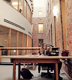 A student studying at a communal space in the Dana Building